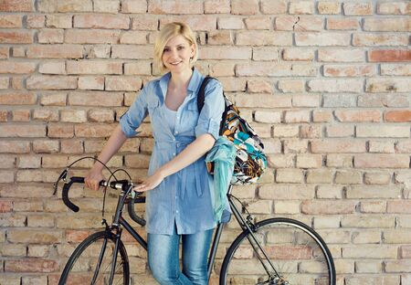 Smiling woman with bicycle front of brick wall. Stockfoto