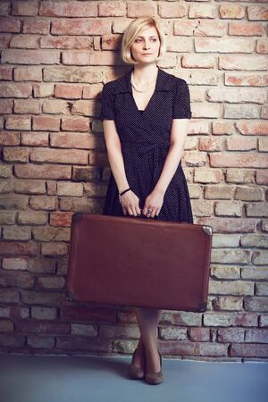 Old-fashioned photo of young woman standing against brick wall, holding suitcase.
