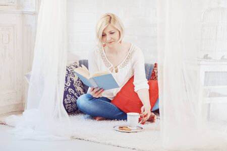Blonde woman sitting at home on floor, drinking coffee, reading a book.