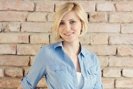 Portrait of happy smiling blond woman looking at camera front of brick wall.