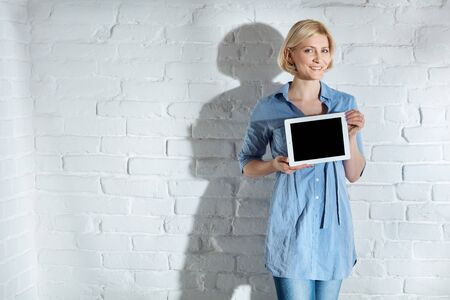Happy woman holding tablet computer with blank screen, smiling, looking at camera. Stockfoto