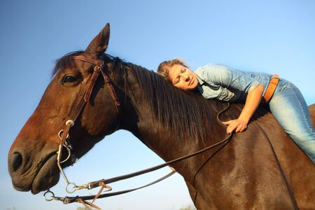 Young woman in jeans lying on horseback, eyes closed.