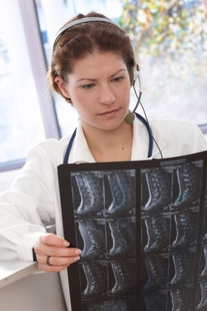 Young female doctor examining medical scan in doctors office.