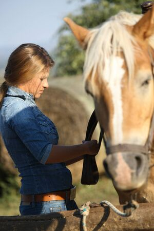 Happy young woman in jeans saddling a horse, smiling.
