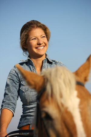 Horse rider portrait. Happy young woman riding on horse, smiling.