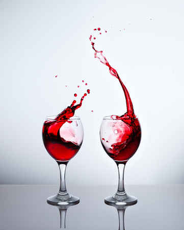 Glasses with red wine and sprays Stock Photo