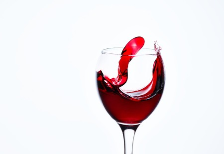 A glass with red wine and sprays. Stock Photo