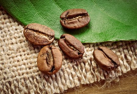 Coffee beans in brown spoon on sackcloth.