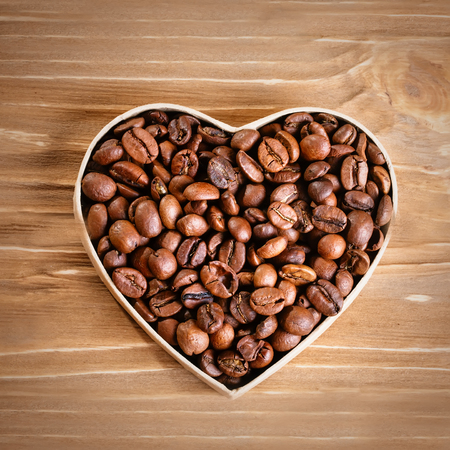 Fried coffee beans lie in the form of heart on wooden boards and burlap. Stock Photo