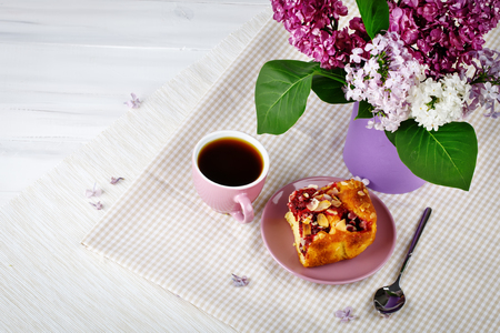 Still life with branches of lilac and a Cup of coffee on a wooden table. Stock Photo