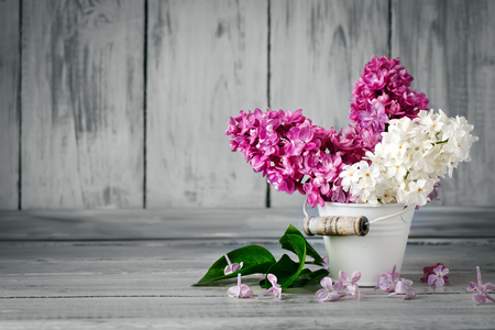 Branches are colored lilac in a basket on the background of wooden boards.