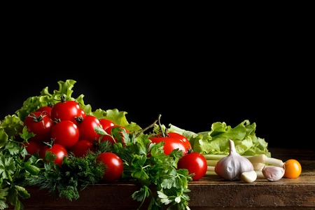 Still life of tomatoes, garlic and parsley on wooden boards. On a black background.