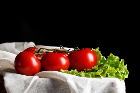 Still life of tomatoes and parsley on wooden boards. On a black background.