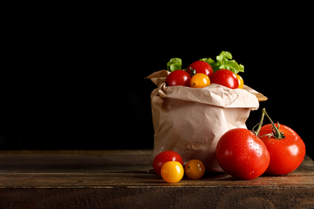 Still life of fresh tomatoes, garlic and parsley on wooden boards. On a black background. Stock Photo