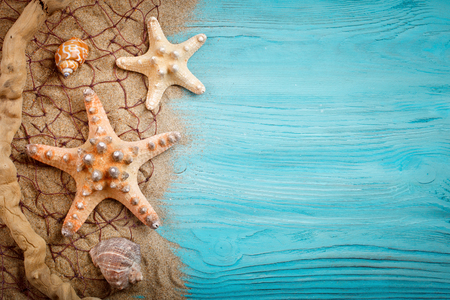 Starfish, pebbles and shells lying on a blue wooden background . There is a place for labels. Stock Photo