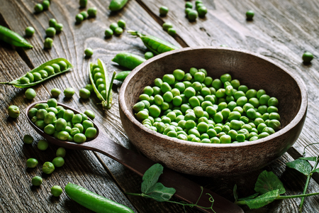 Delicious ripe green peas lying on a wooden table.