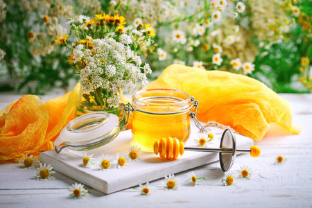 oriented: Tasty and healthy honey on white wooden table with flowers of chamomile. Stock Photo