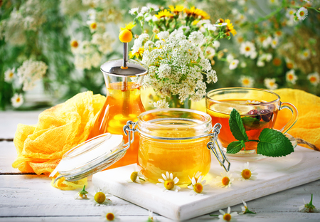 A healthy Cup of tea, a jar of honey and flowers. Selective focus. Stock Photo