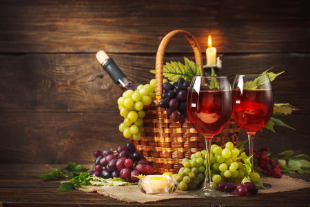 Basket with fresh grapes and a glass of wine on a wooden table. Autumn background. Standard-Bild