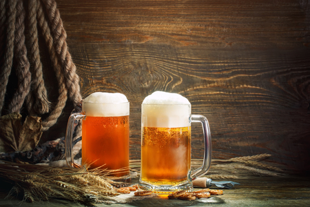 Glasses of fresh beer on a wooden table.