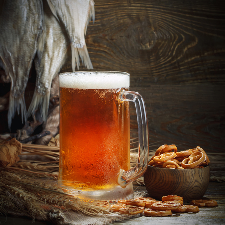 A glass of beer and dried fish on a wooden table.