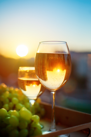 bebes lindos: Glasses with white wine at sunset, with the reflection of the houses. Foto de archivo