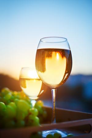 bebes lindos: Gafas con vino blanco al atardecer, con el reflejo de las casas. Foto de archivo