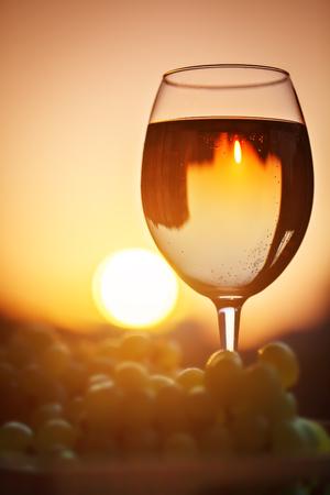 bebes lindos: Un vaso de vino blanco al atardecer, con el reflejo de las casas.