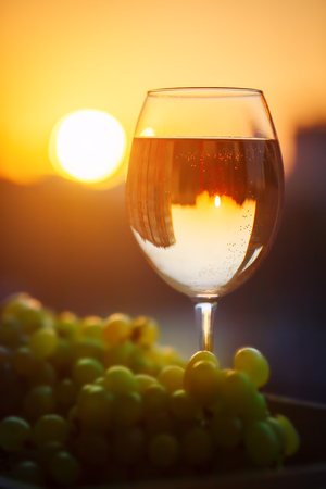 bebes lindos: A glass of white wine at sunset, with the reflection of the houses.