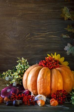 De houten tafel versierd met groenten, pompoenen en herfstbladeren. Herfst achtergrond. Schastlivy von Thanksgiving Day. Stockfoto