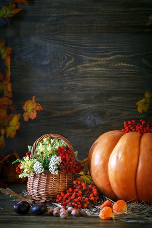 The wooden table decorated wild with flowers by pumpkins and autumn leaves. Autumn background. Happy Thanksgiving Day background.