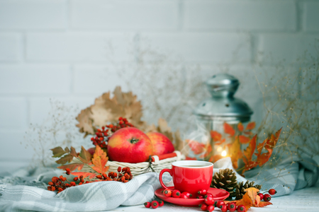Cup of coffee, apples and autumn leaves on a wooden table. Autumn background. Stock Photo
