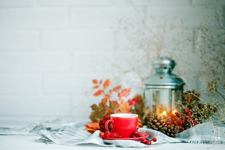Cup of coffee, cones, berries and autumn leaves on a wooden table. Autumn background. Stock Photo