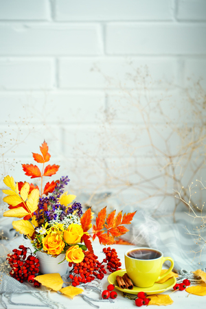 Cup of coffee, autumn leaves and flowers on a wooden table. Autumn still life. Selective focus. Stock Photo