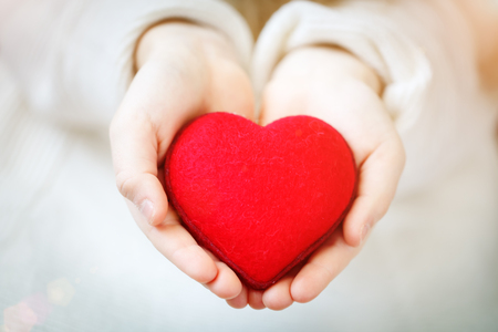 Red heart in hands of the little girl. Symbol of love and family.Valentines day card. Mothers day. Backgrounds for social posters. Selective focus.
