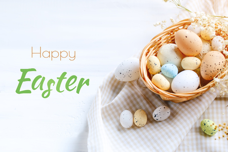 Happy Easter. Congratulatory easter background. Easter and quail eggs on a wooden table.
