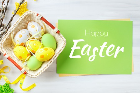Happy Easter. Congratulatory easter background. Easter eggs and flowers. Background with copy space. Stock Photo