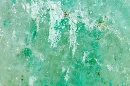 The mineral is jadeite. The texture of the mineral. Macro shooting of natural gemstone. The raw mineral. Abstract background.