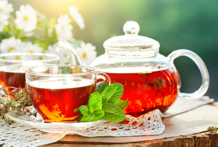 Cup with hot tea with mint and a thyme on a wooden table in a summer garden.