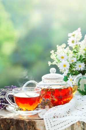 Cup with hot tea with mint and a thyme on a wooden table in a summer garden. Selective focus,