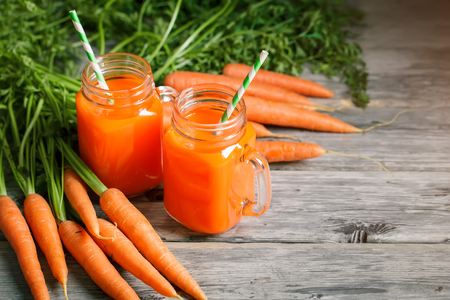 Fresh Carrot and carrot juice on Wooden Table in Garden. Vegetables Vitamins Keratin. Natural Organic Carrot lies on Wooden background. Rustic Style.Harvest. Selective focus, Background with copy space