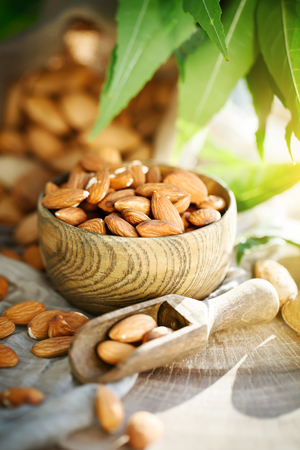 Almond on a wooden table in the summer garden. Useful food. Stock Photo
