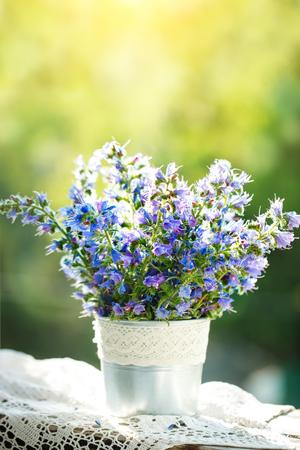 Beautiful purple flowers in a vase in a summer garden. Summer still life.