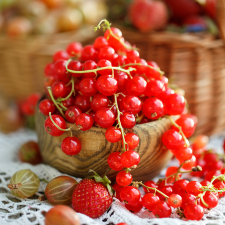 Ripe red currant on a wooden table in the garden.