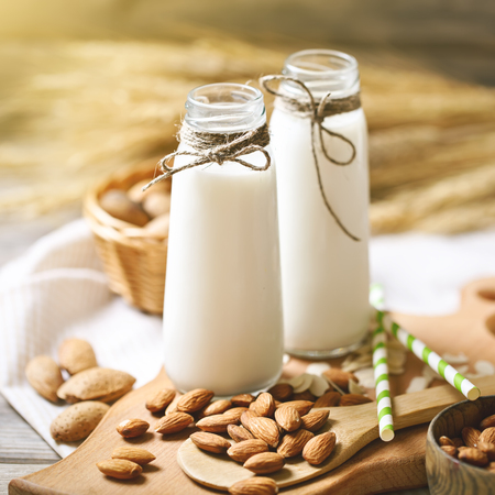 Almond and almond milk on a wooden table in the summer garden. Useful food.