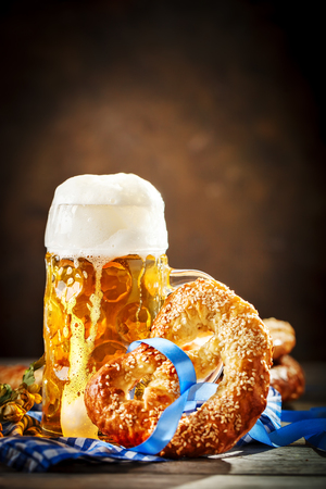 Beer mugs and pretzels on a wooden table. Oktoberfest. Beer festival. Selective focus. Background with copy space.