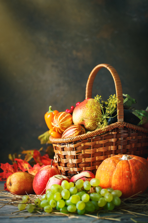 Happy Thanksgiving Day background, wooden table decorated with Pumpkins, Maize, fruits and autumn leaves. Harvest festival. Selective focus. Vertical. Background with copy space.