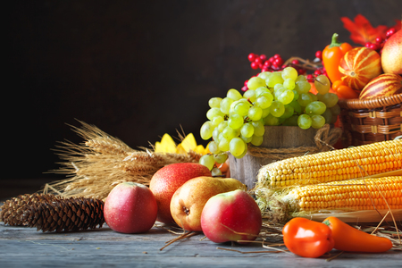 Happy Thanksgiving Day background, wooden table decorated with Pumpkins, Maize, fruits and autumn leaves. Harvest festival. Selective focus. Horizontal. Background with copy space.