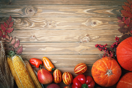 Happy Thanksgiving Day background, table decorated with Pumpkins, Maize, fruits and autumn leaves. Autumn festival. Harvest festival. The view from the top. Horizontal. Background with copy space.