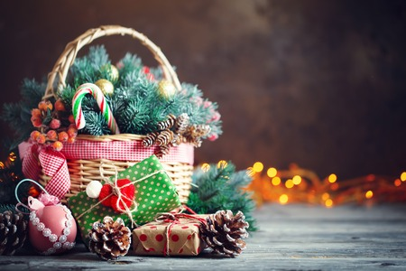 Merry Christmas and happy new year. Basket with Christmas toys and Christmas gifts on a wooden background. Standard-Bild